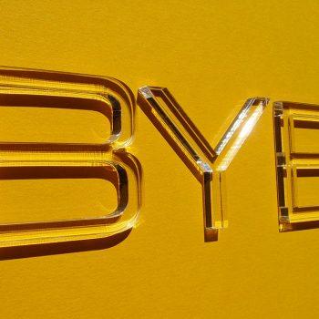 Buchstaben aus durchsichtigem Plexiglas in 3mm Materialstärke auf gelbem Hintergrund